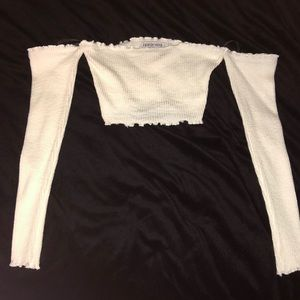 Fashion Nova white crop top with long sleeves.